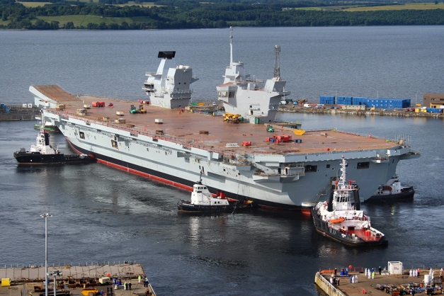 The Royal Navy's largest ever warship HMS Queen Elizabeth is gently floated out of her dock for the first time in Rosyth, Scotland.